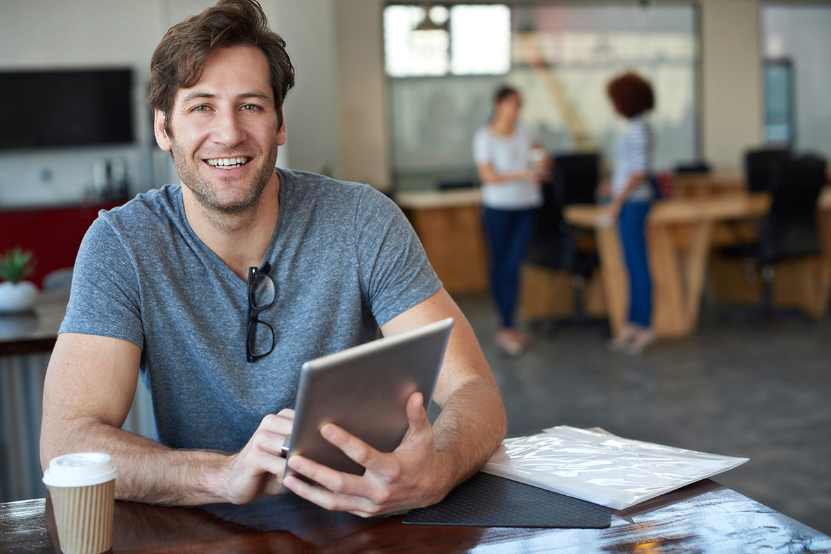 Man smiling with tablet in hand