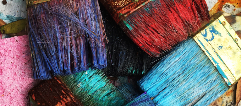pile of paintbrushes covered in colored paint